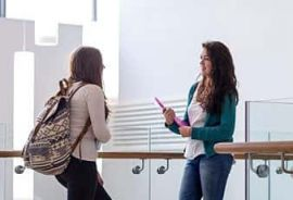 Two female university students chatting face to face