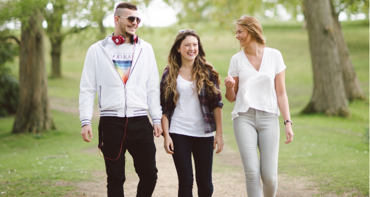 3 students strolling along a path surrounded by trees on the University of Essex campus