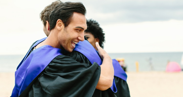 Graduates on the beach hugging while wearing caps and gowns