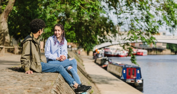 Students chatting by the River Ouse