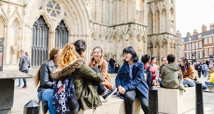 International students relaxing in front of York Minster cathedral