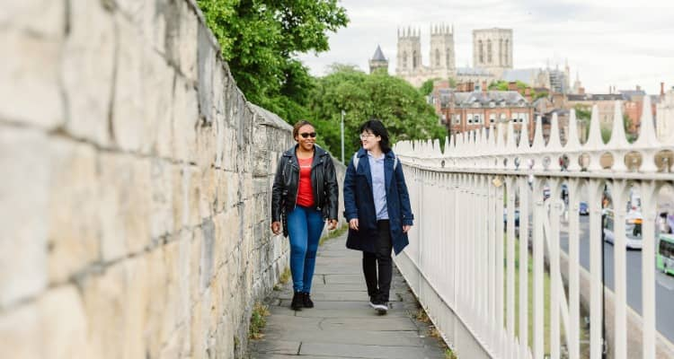 Students walking along the city walls in York