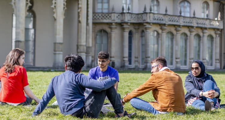 students laying in the grass in front of Brighton Pavilion