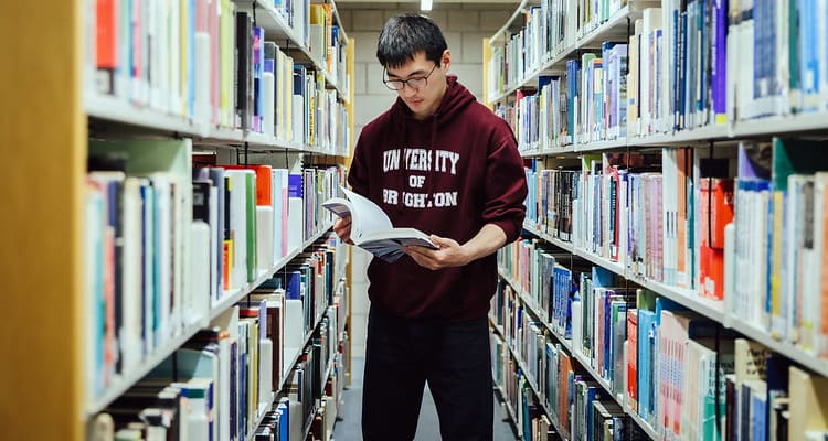 student reading a book in library