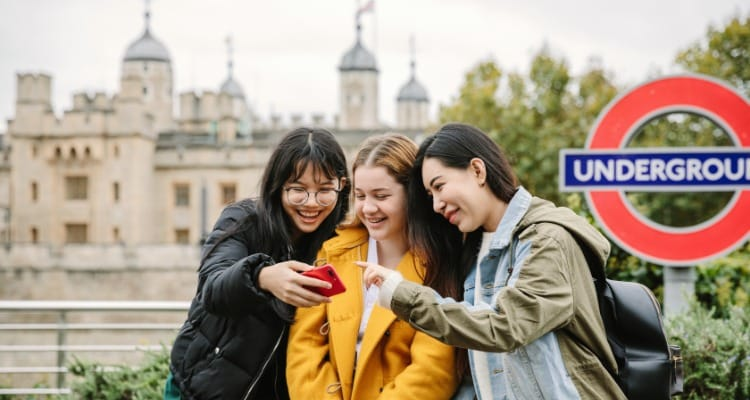 Three students students outside the Tower of London smiling at a mobile phone, in why study in the UK