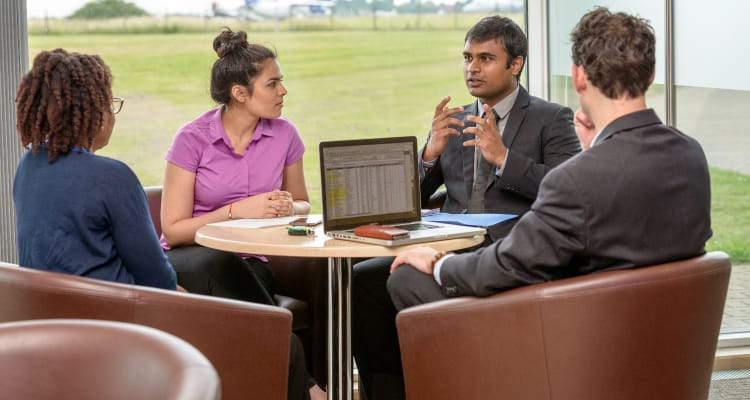 Cranfield students gathered around a table with a laptop open showing a spreadsheet.