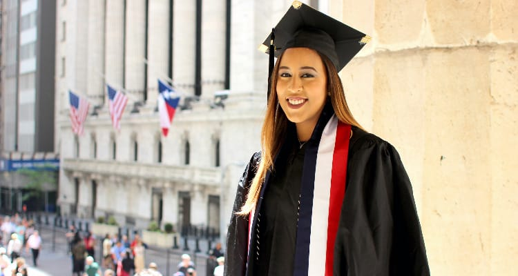 OPT: A young woman with long, light brown hair in graduation robes, outside a building with the US flag flying outside