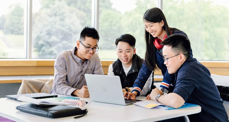 OPT: Chinese students gathered around a laptop, looking at the screen and smiling
