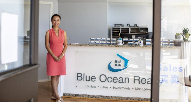OPT: A woman in a coral dress standing smiling outside a realty office