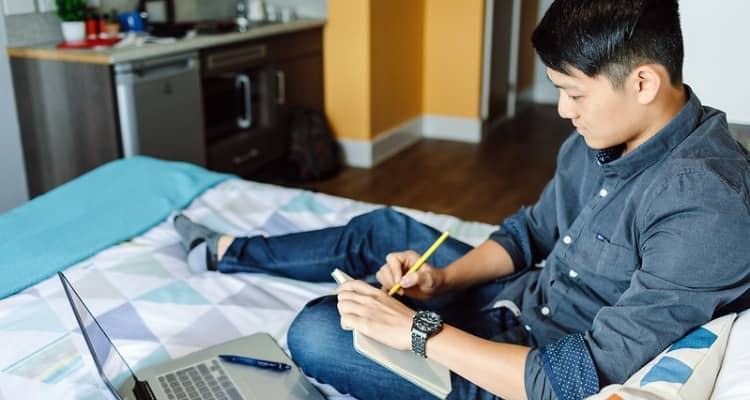 A young man studies in his bedroom with a laptop and notepad
