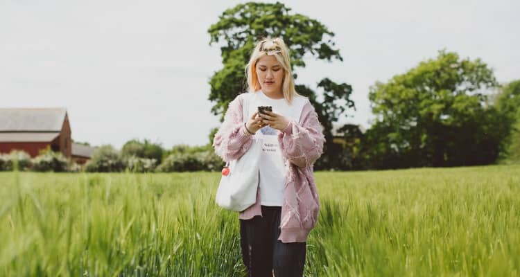 A young woman walks through a field while looking at her phone