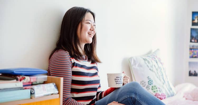 A young woman drinks a cup of coffee in her room and smiles