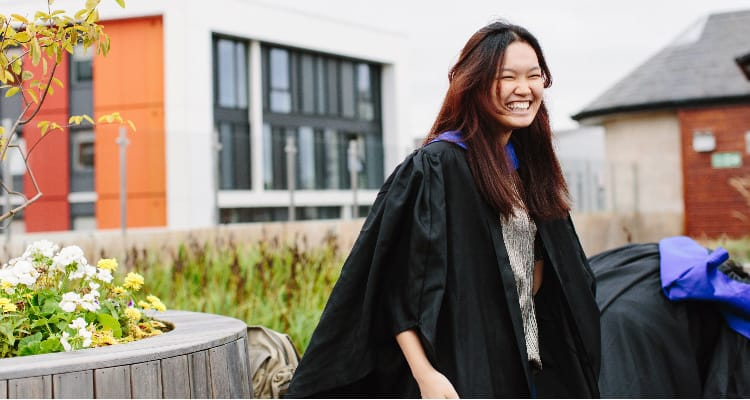 A smiling student wearing a graduation gown