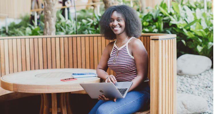 A young, black, female student sitting in a booth on the University of Essex camous, smiling while holding a laptop. There is a notepad and pen on the table.