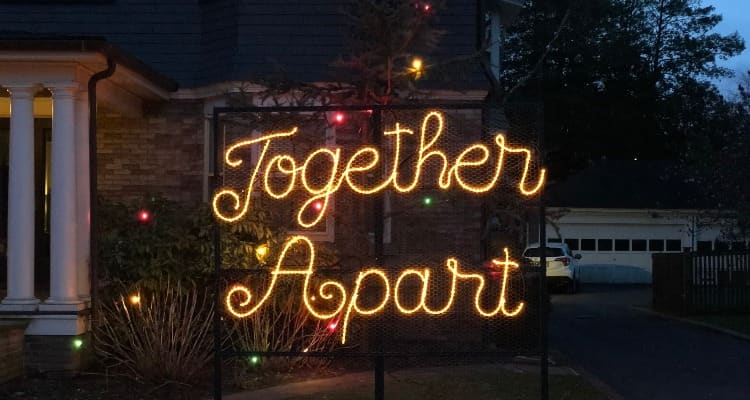 """The words """"Togther, Apart"""" in lights on a front lawn"""