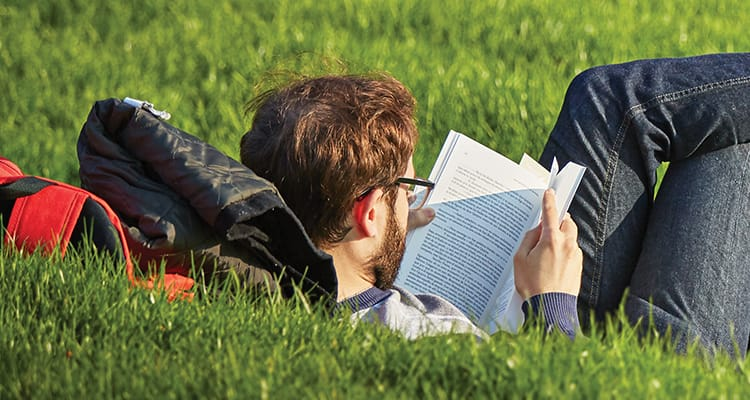 young man with brown hair and glasses laying on a red backpack on grass reading a book