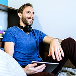 Male student in blue T-shirt and black jeans lounging with a tablet device