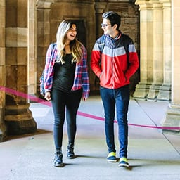 Blonde female and brunette male university students walking side by side looking at each other